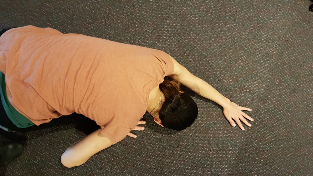 Kneel and bend forward reaching out with your hands. Keep your buttocks resting on your feet and lower your head to the ground. Move one arm toward to the other side to feel stretching in the latissimus dorsi.