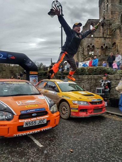 Jumping Jock at Jedburgh - Holy Socks rally driver Jock Armstrong celebrates in traditional style after winning the Brick and Steel Border Counties Rally.  In the background are the ruins of Jedburgh Abbey - what would the monks have thought?