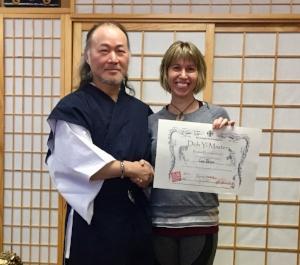 Lara with Grandmaster Sung Baek receiving her 10,000 Doh Yi Training Certificate in Dec. 2017.