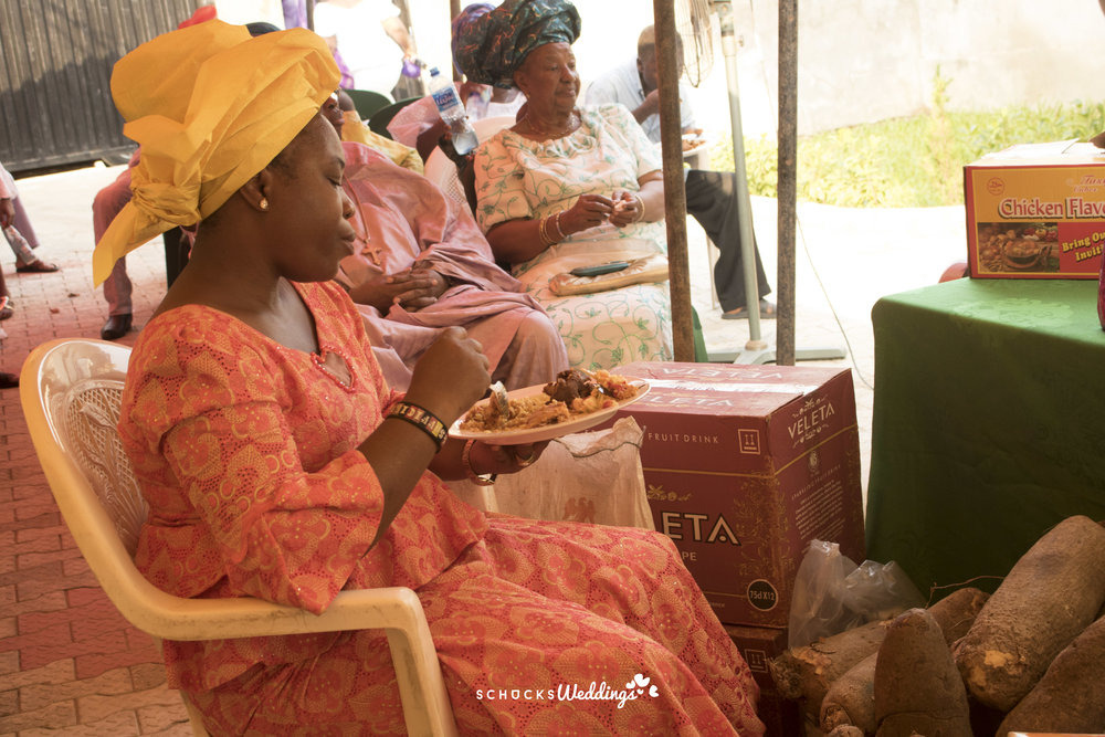 A lady sitting really close to the souvenirs at a traditional wedding