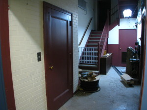The elevator is the door at the left. The stairs ahead have a more than usual steep pitch.