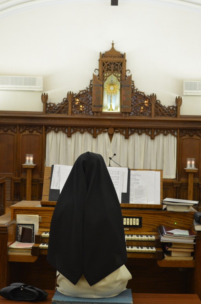 Sr. Mary Veronica practices the organ. Note the atlas our organists are using to raise the height of the temporary bench!