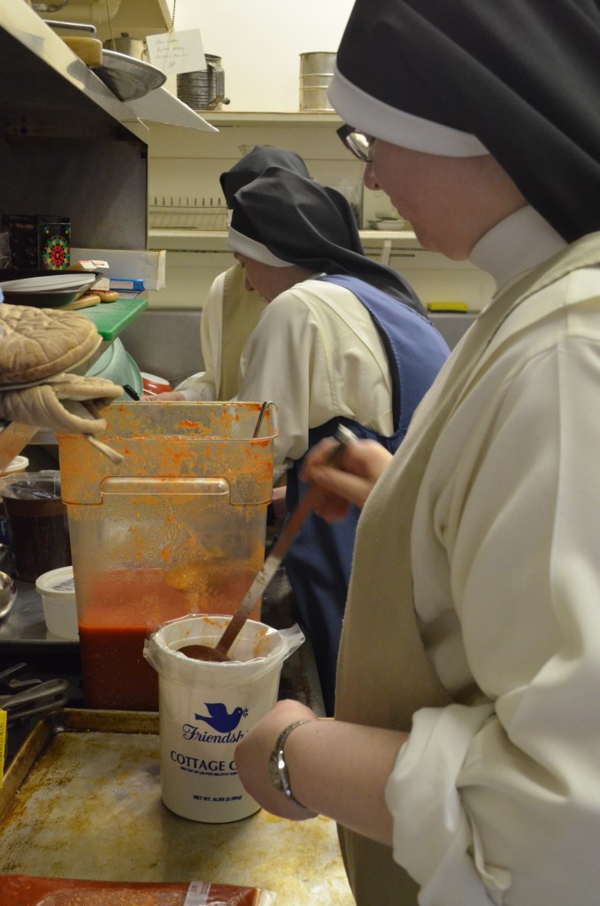 Sr. Judith Miryam, Sr. Mary Magdalene, and Sr. Mary Amata ladle sauce into freezer bags.