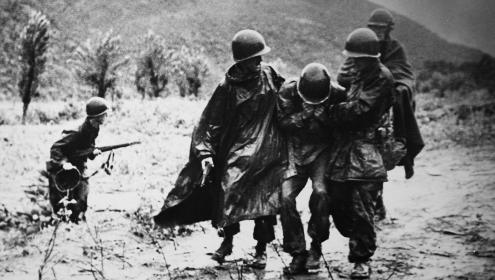 Fr. Kapaun, second from the right, helps a soldier.
