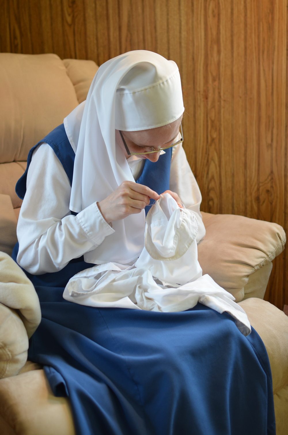 Sr. Maria mends her blouse.