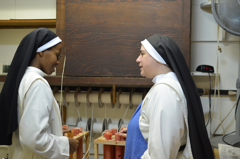 Sr. Mary Catharine (R) shows Sr. Francisca our candle department. Sr. Francisca makes candles at her monastery in Kenya.