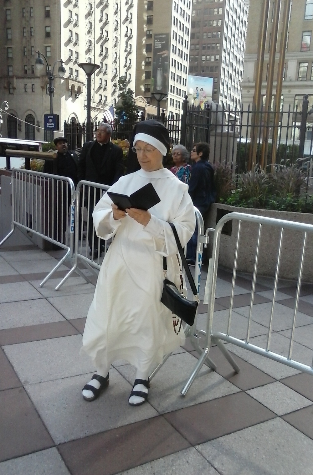 Sr. Denise Marie prays the Divine Office while waiting. Earlier they greeted every Cardinal and Bishop attending who passed them going by the barriers behind Sister!