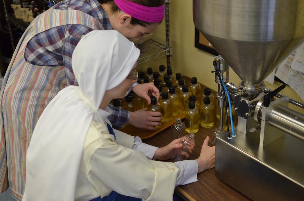 Our aspirant, Marie, helps Sr. Maria Johanna fill and cap liquid soap.