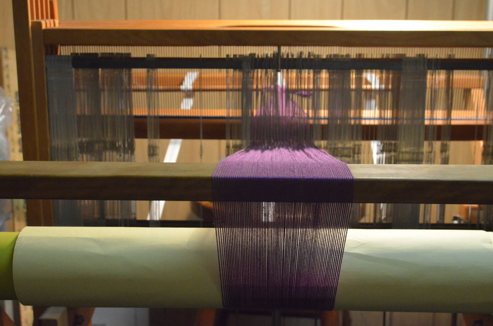 4) The most complicated part of the process (...besides possibly the calculations...) is warping (or dressing) the loom. Each thread must be carefully pulled through the beater (seen below) and a heddle (those vertical metal things in this picture), arranged specifically for the desired pattern. Once the warp is fastened to the back of the loom, an intricate process is used to roll up the warp, making sure tension is kept steady and even.  The front is tied off and we're ready to begin!