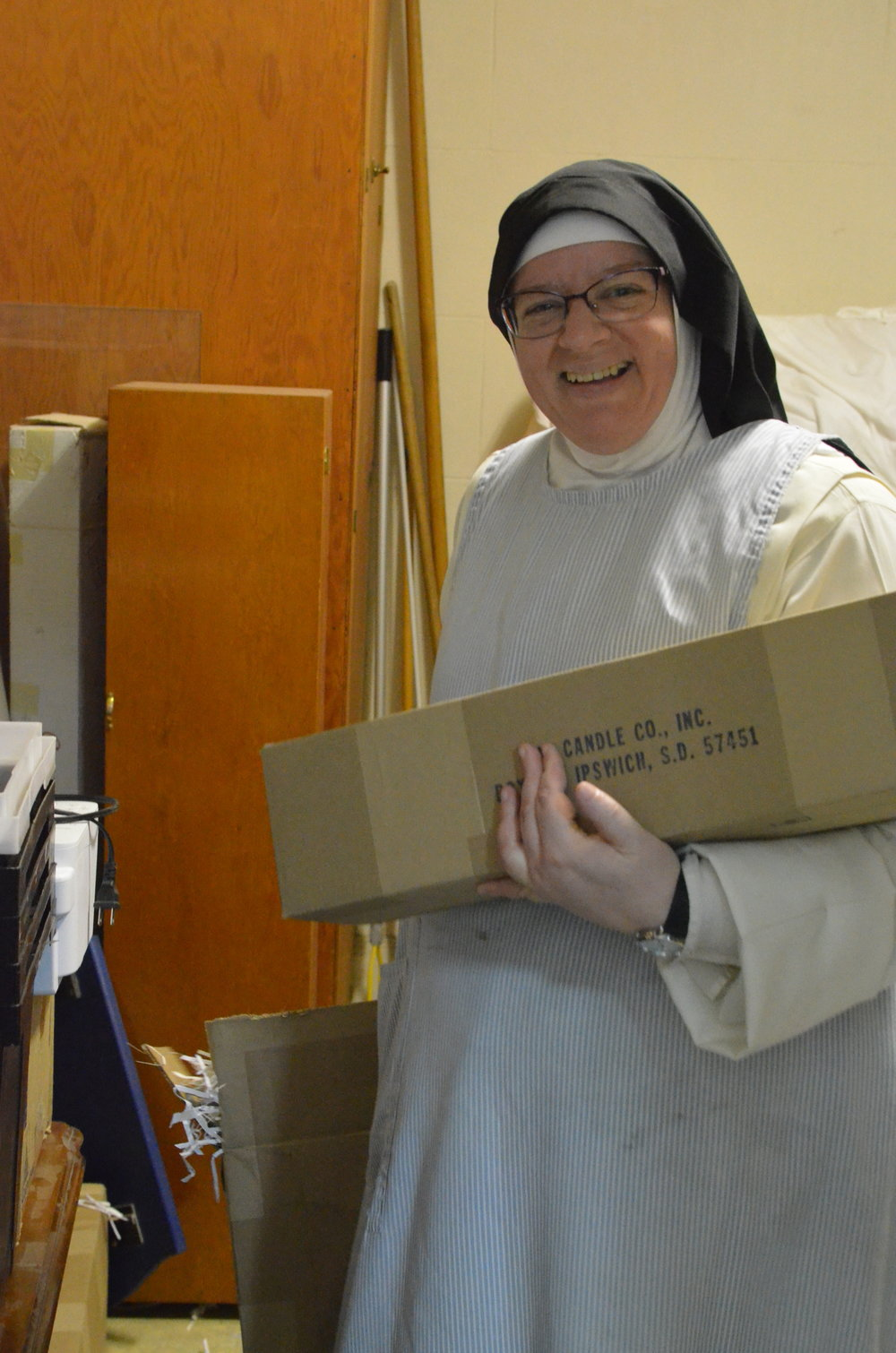 Sr. Judith Miryam, the sacristan, bringing up candles from the sacristy store room