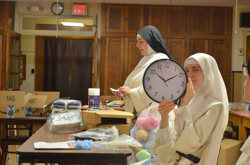 Sr. Lucia Marie shows off one of the clocks