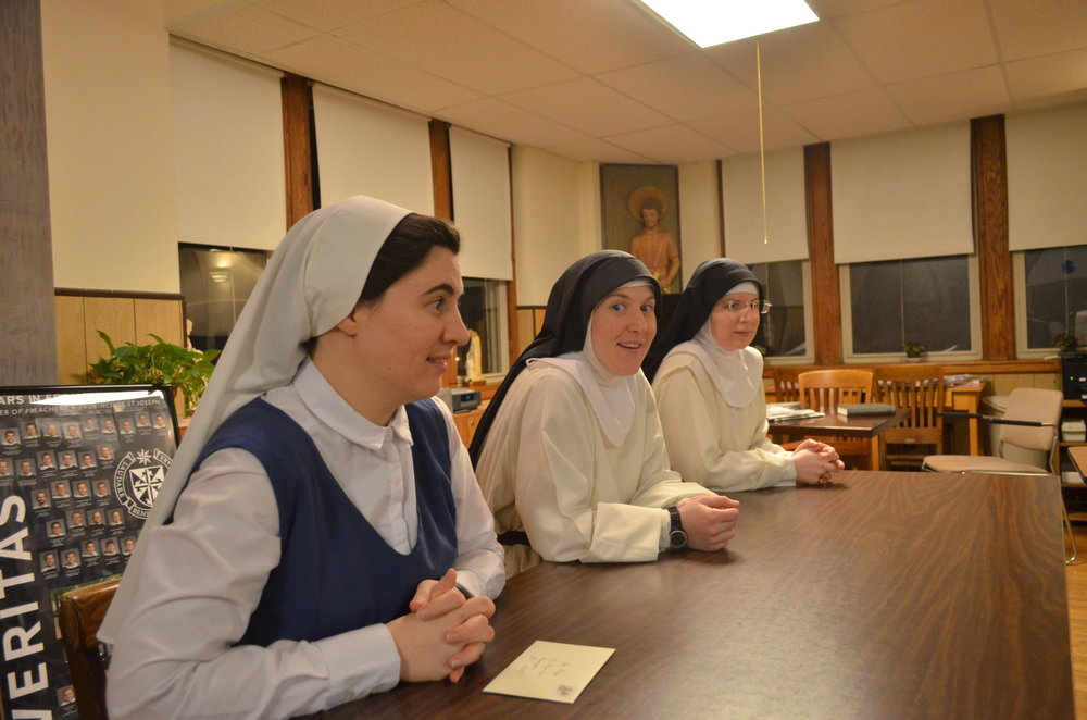 Sr. Lauren, Sr. Mary Magdalene, and Sr. Mary Veronica watch the unboxing