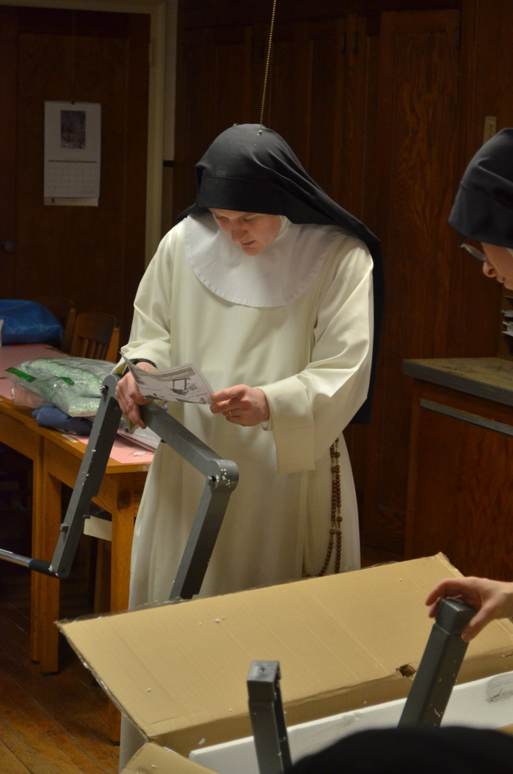 Sr. Mary Magdalene studies the instructions for the cleaning cart