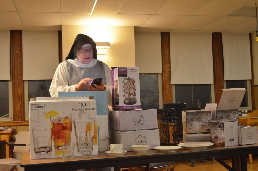Sr. Judith Miryam reads off the names of the purchasers of the tableware/glassware