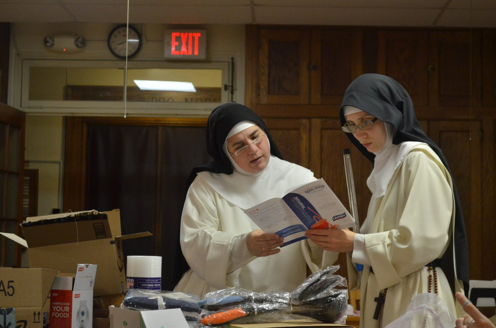 Sr. Mary Catharine and Sr. Maria Johanna study the instructs for the mop