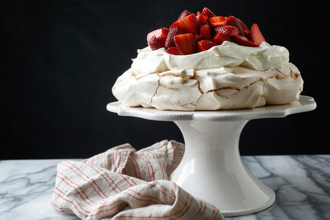 Photo Credit: Craig Lee for The New York Times   Strawberry Pavlova   NIGELLA LAWSON    YIELD 6 servings   TIME  2 hours   INGREDIENTS  FOR THE MERINGUE:   4   egg whites     Pinch of salt    1 ¼   cups superfine sugar    2   teaspoons cornstarch    1   teaspoon white-wine vinegar     A few drops vanilla extract   FOR THE TOPPING:   1   pound strawberries, hulled and halved or quartered    ½   teaspoon high-quality vanilla extract    1   teaspoon high-quality balsamic vinegar    2   teaspoons superfine sugar    2   cups heavy cream   PREPARATION  To prepare meringue: heat oven to 350 degrees. Line a baking sheet with parchment paper, and draw a circle on the paper using an 8- or 9- inch cake pan as a guide. Flip the parchment over so the pencil marking is facing down (this ensures that the pencil won't transfer to the meringue). In bowl of an electric mixer, combine egg whites and salt. Begin beating at low speed, slowly increasing to high. Continue until satiny peaks begin to form; gradually beat in sugar a tablespoon at a time until meringue is stiff and shiny.  Sprinkle in cornstarch, white-wine vinegar and vanilla, and fold in gently. Mound onto parchment within circle, and shape into a disk, flattening top and smoothing sides. Place in oven, and immediately reduce heat to 300 degrees. Bake 1 hour 15 minutes. Turn off heat, and allow meringue to cool completely in oven.  To prepare topping: in a mixing bowl, combine strawberries, vanilla, balsamic vinegar and sugar. Cover with plastic wrap. Let sit at room temperature at least 15 minutes and up to 2 hours.  To serve, carefully peel off parchment and place meringue on a platter or cake stand. Gently crack the top with the back of a soup spoon to make a shallow nest for the whipped cream and berries. Whip cream until it is thick enough to hold peaks, and spoon it evenly over meringue. Cover cream with strawberries, allowing a small amount of their liquid to dribble onto cream. Serve immediately.