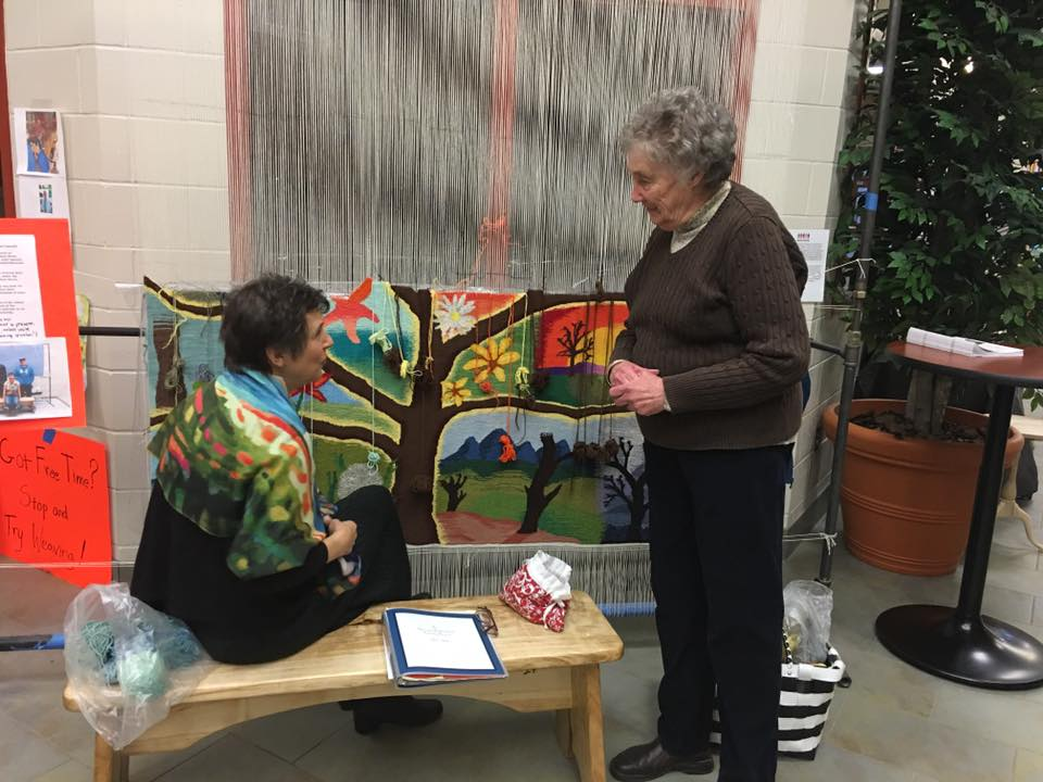 Rebecca Powell, an Enfield tapestry weaver, has collaborated with Experiencing the Arts in Art Design class to create from the students' nature themed designs a beautiful-to-be 4x6 foot tapestry to hang in the new media center. Woodshop students built the loom for her and Friends of Mascoma Foundation is happy to fund all the materials for all of our artists through our above mentioned sources. Becky can be found most weeks in the front entrance halls of the MVRHS and welcomes a visit from you. Margaret LeVesque a volunteer from Enfield is also pictured.