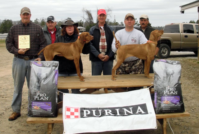 "Shooting Dog  Dogs left to right: runner up - FC AFC Burr Oak's Quarterback (""Rex""); winner - Touchdown Kid's Jet City Rose (""Rosie"") People left to right: Brian Gingrich, Gus Toombs (judge), Theresa Gimbut, Mark Johnson, Brian long, and Ben Lorenson (judge)"