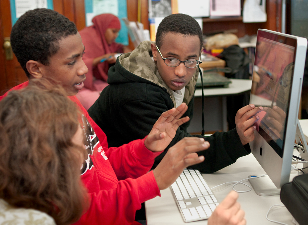 Student team discusses video project with media teacher