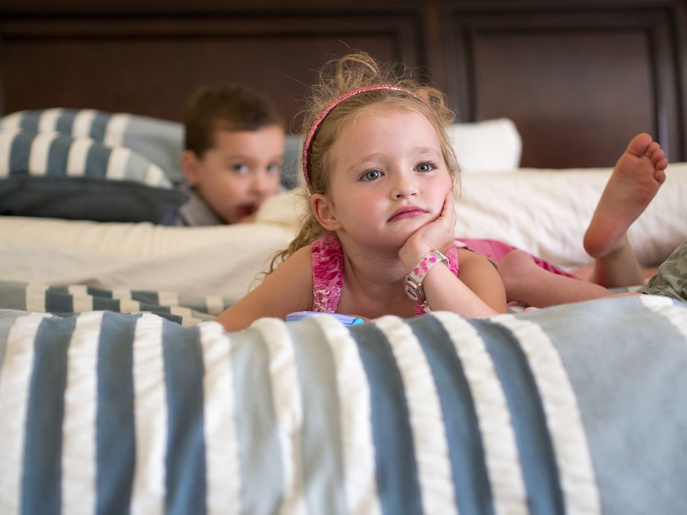 Siblings watch TV on their parents' bed