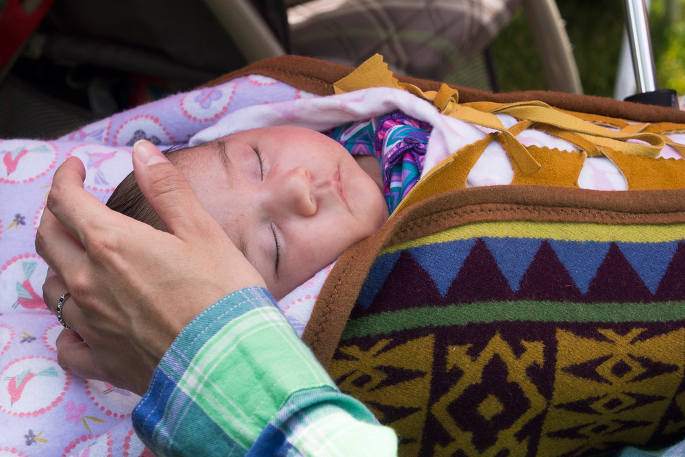 Baby sleeps peacefully under mother's watch during a Pow Wow