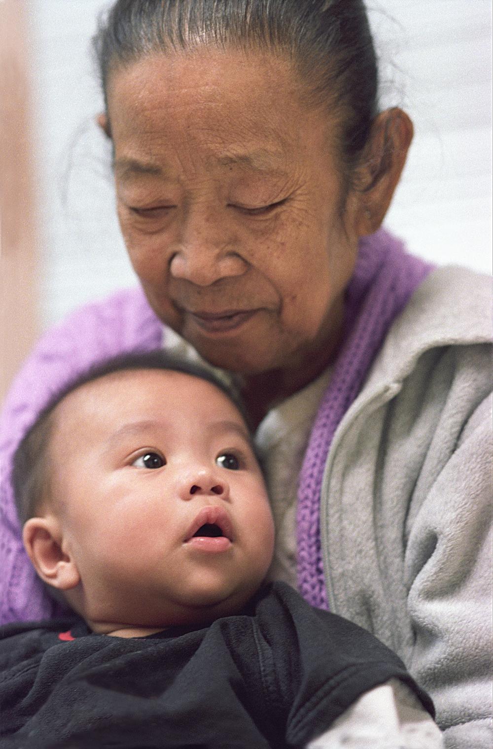 Southeast Asian grandmother holds her grandson, Harborview Medical Center International Clinic