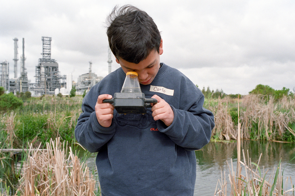 Elementary student looks at water sample collected at Mt. View Marsh adjacent to water treatment plant, Mt View Marsh Education Program