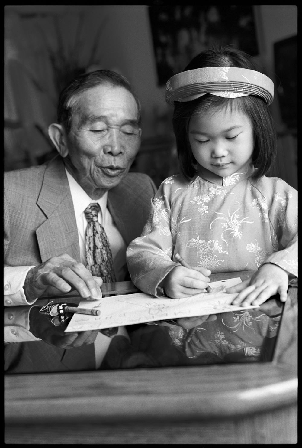 Vietnamese grandfather admires his American born granddaughter's drawing, Key LInks