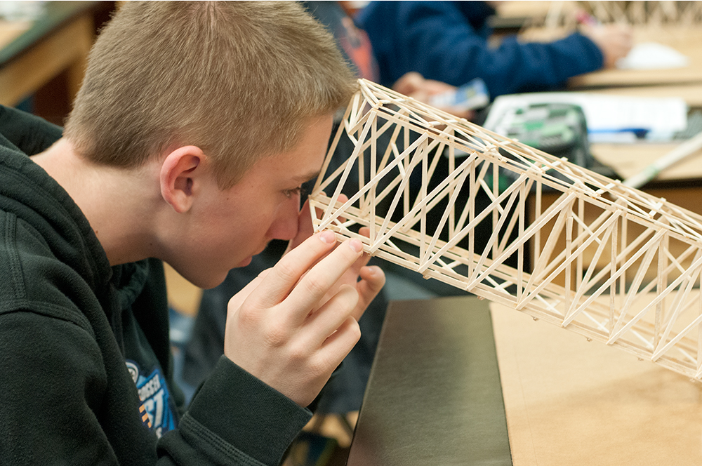 Highs school student examines the bridge he constructed in science class, The Northwest School