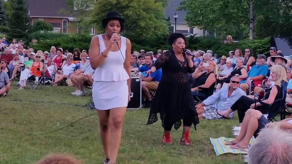 Janelle and Mae singing to the crowd