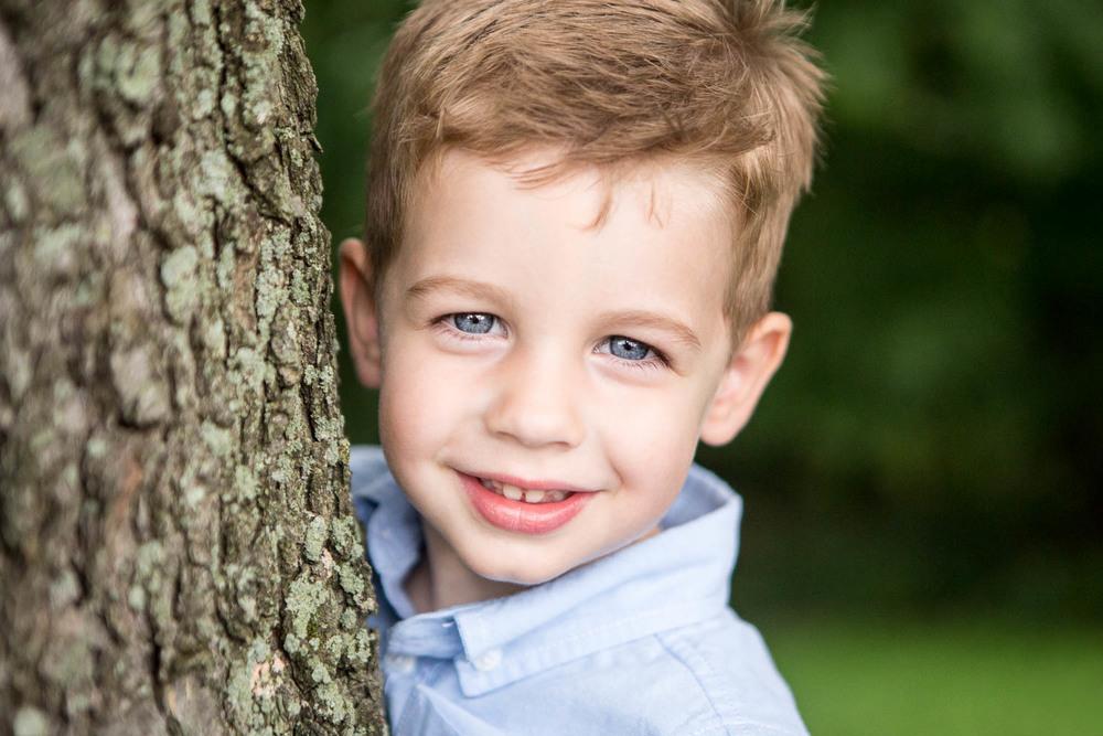 Portrait of a little boy by a tree trunk