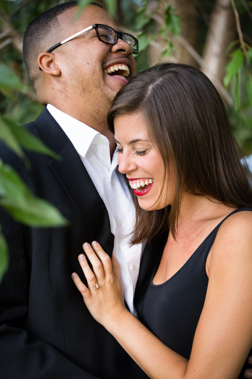Photo of a laughing interracial couple dressed up under the trees