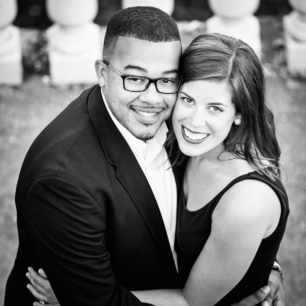 Black and white photograph of an interracial couple looking up into the camera
