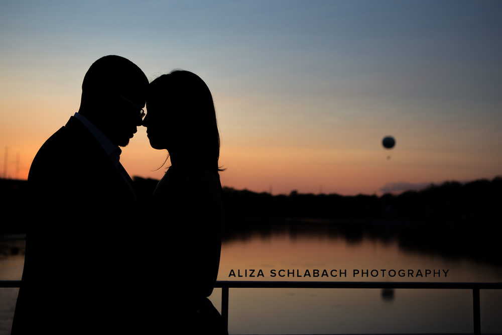 Silhouette of a couple at dusk in front of Philadelphia's boat house row