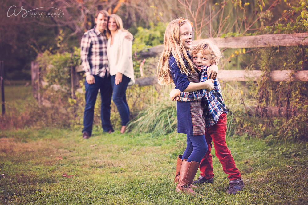 Autumn family portrait with parents in the background, and little girl and boy hugging each other in the foreground