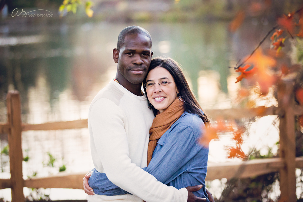 Photograph of an interracial couple embracing in front of a pond