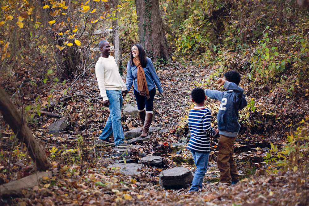 Fall photo of parents and their 2 kids crossing a stream