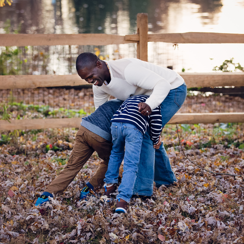 Photo of a black dad playing with his kids by a pond