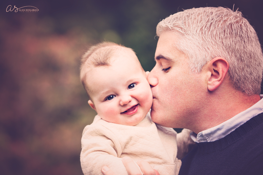 Close up outdoor photo of silver haired dad kissing his smiling baby's cheek