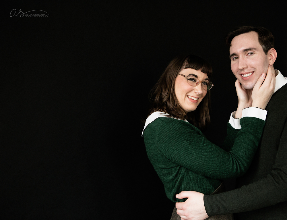 photo | girl with hands around her fiancé's face | engagement portrait at Aliza Schlabach's Ardmore photography studio