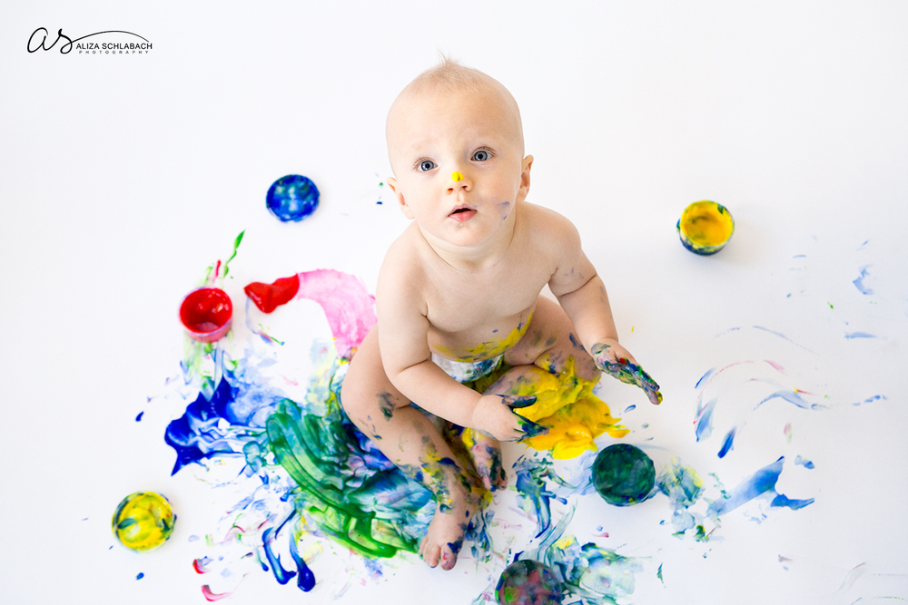 Photo of one year old baby playing with finger paint on white background