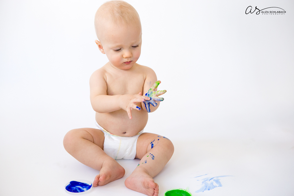 Photo of one year old baby boy examining fingerpaint on his hand