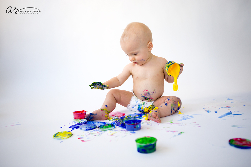 Photo of one year old boy unknowingly spilling fingerpaint
