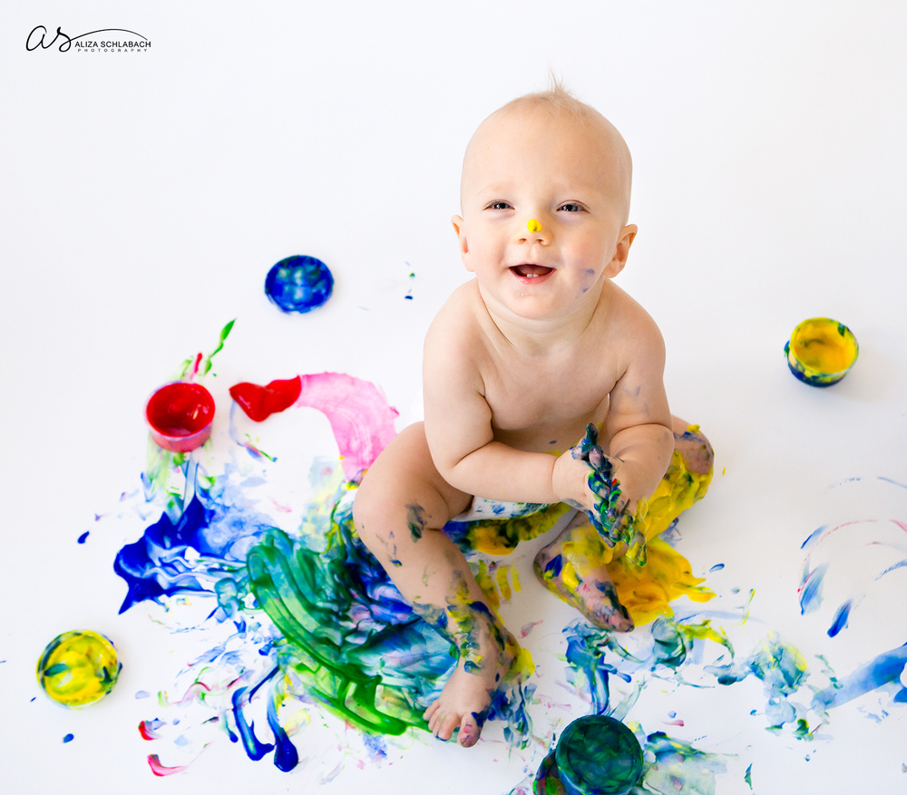 Photo of smiling one year old baby boy fingerpainting and lookup up at camera