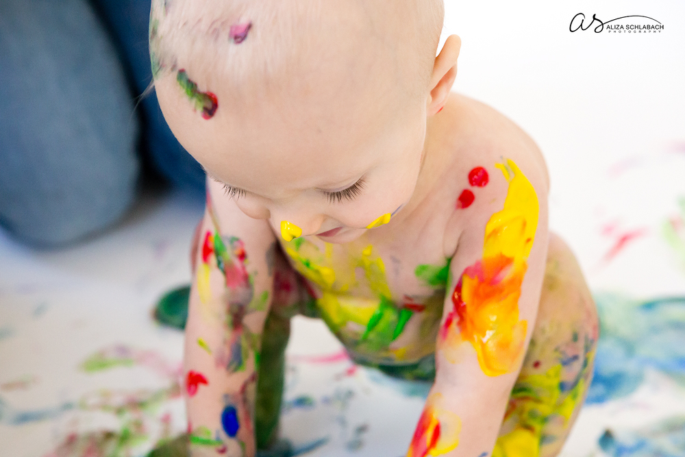 Close up photo of one year old covered in fingerpaint