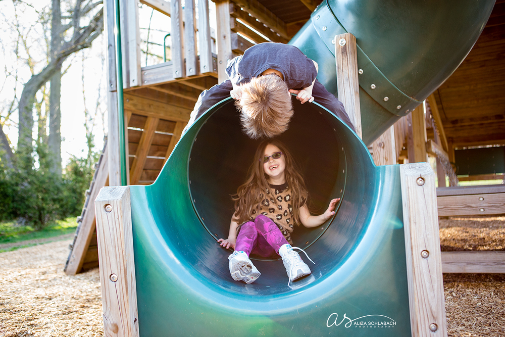 Photo of brother and sister playing on slide