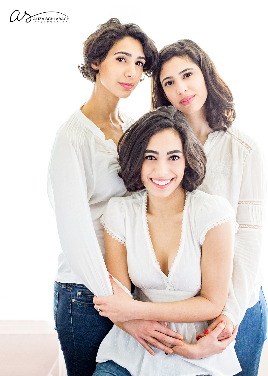 Backlit portrait of three beautiful grown sisters all in white