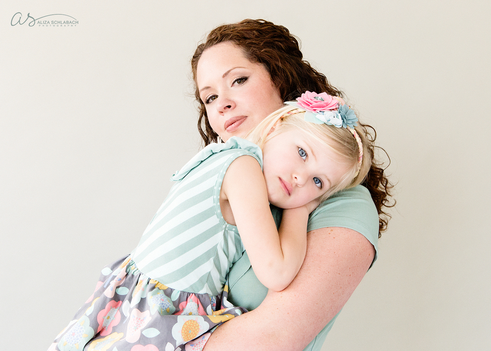 Studio portrait of a mother holding her young blonde daughter