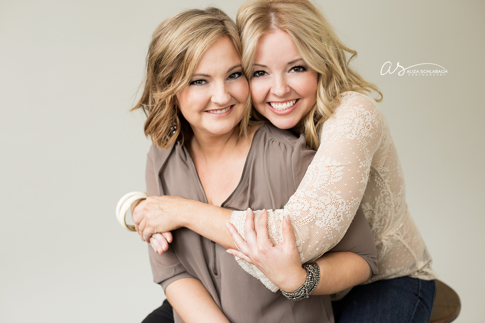 Studio portrait of two grown sisters embracing