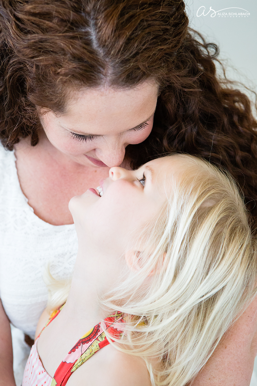 Photo of mother and little blonde daughter nose to nose